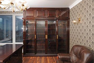 Тёмный шкаф из массива дерева для кабинета со стеклянными дверцами