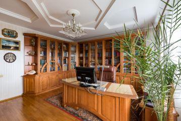 Угловой кабинет с книжными шкафами и столом из массива дерева