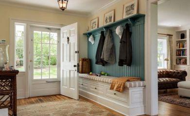Прихожая из массива дерева с мягкой обивкой мебели и крючками для одежды